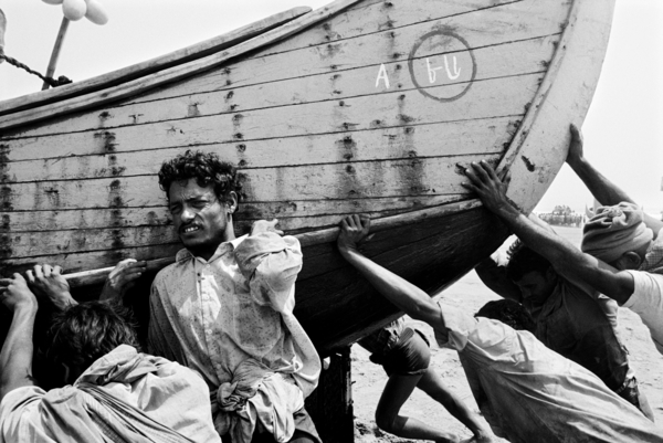 A group of Rohingya men push their fishing boat back onto shore. Most Rohingya men in the Shamlapur area of Bangladesh work as bonded labourers and are trapped into debt by local Bangladeshi boat owners (2008). Copyright: Greg Constantine