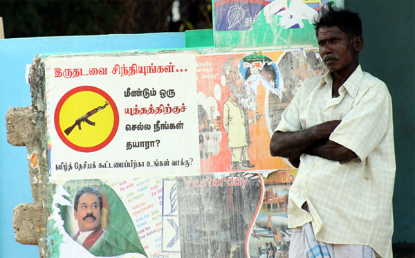 A man standing in front of pro-Rajapaksa and anti-Tamil National Alliance campaign ads posted ahead of the Northern Provincial Council elections. Flickr / Vikalpa | Groundviews