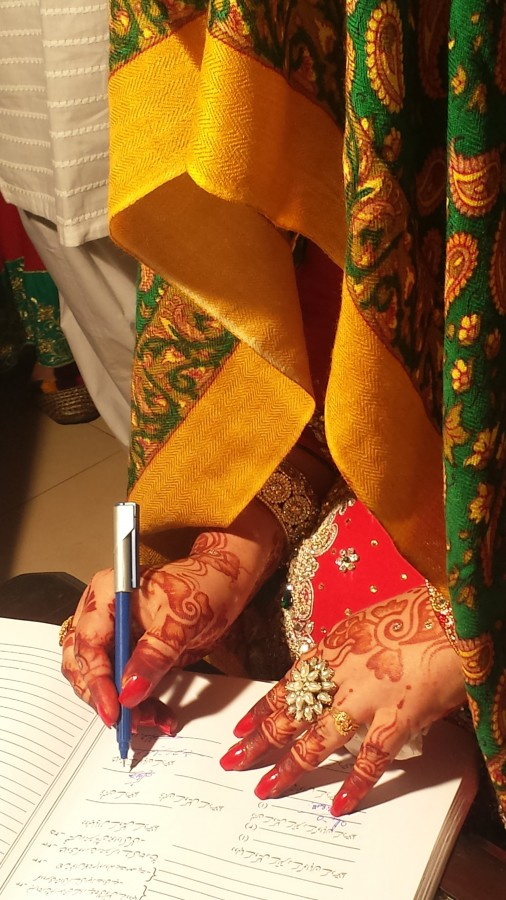 A bride signing a marriage certificate in Urdu. Many British Southasians choose to marry partners from Southasia. Photo : Wikimedia Commons / S.M. Samee