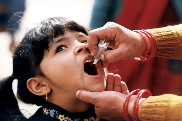 Girl receiving oral polio vaccine. Photo : Flickr / CDC Global
