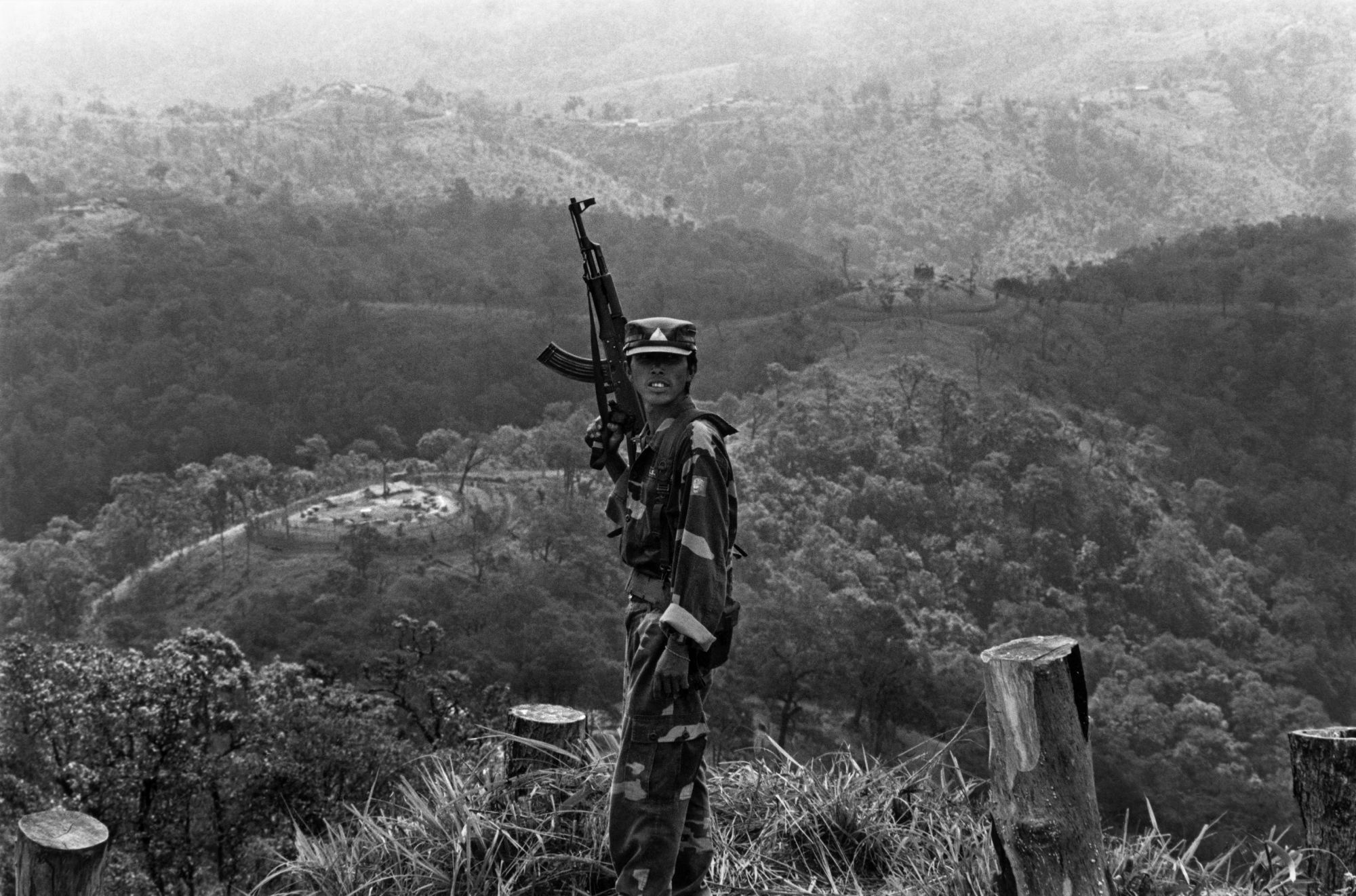 A soldier of the Shan State Army stands guard on the frontline. Behind him is a hill top outpost belonging to the United Wa State Army, who were allies of the Burmese military and Burma's largest drug cartel. The Shan have been fighting for an independent state for decades. December 2005.