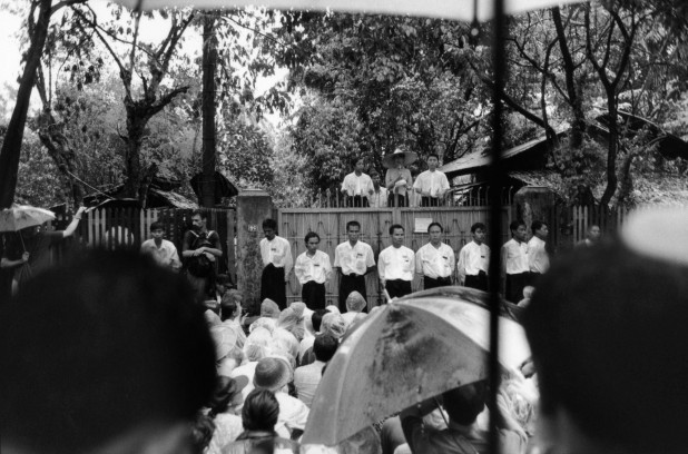 Flanked by her body guards, Suu Kyi addresses her supporters at the gate of her home on University Avenue. The following year, these speeches were prohibited altogether and many youth members of the NLD fled to neighbouring Thailand, fearful of arrest. Rangoon.