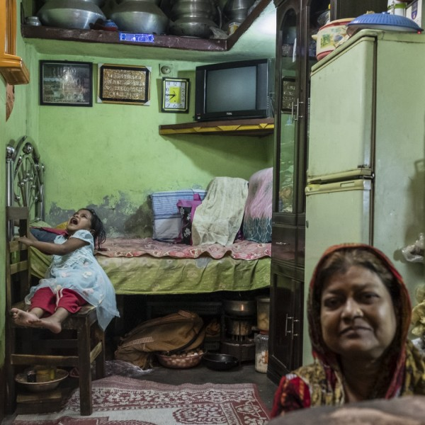 A woman and child inside their one-bedroom house in Geneva Camp. Over 40 years after the Liberation War, many families are still living inside 8 x 8 single room houses.