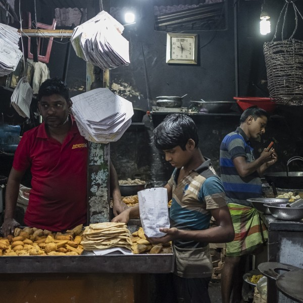 A boy working for a street-food vendor packs food into a paper bag.