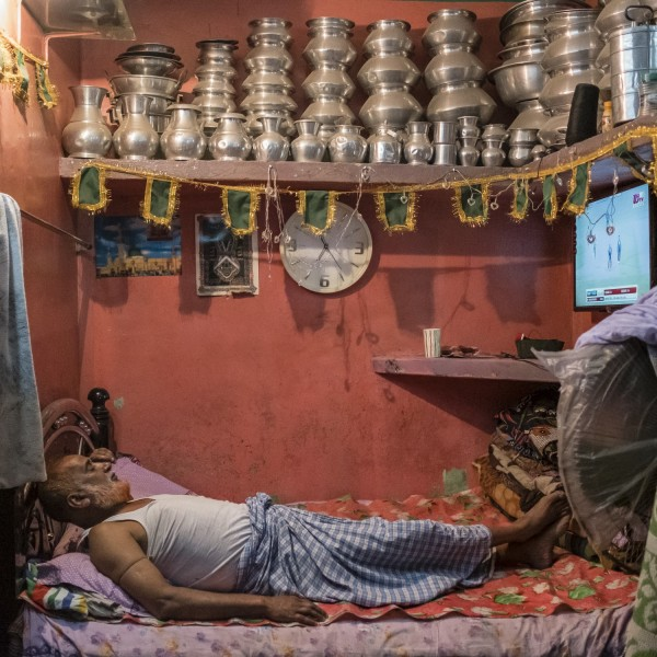 A man watches a cricket match from his bed at home.