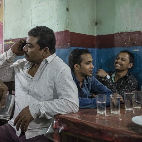 Men socialising over dinner at a restaurant in the camp.